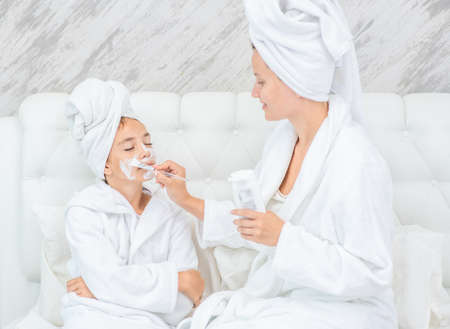 Young mother puts white cream on her smiling daughter's face at home. Imagens - 155155343