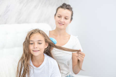Happy family at home. Young mom cares for her daughter's hair by combing it in morning. Imagens - 155155157
