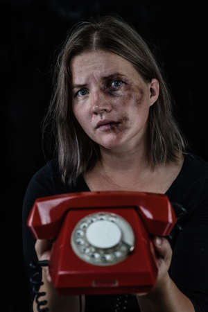 Woman victim of domestic violence and abuse holds a phone in her hands. Isolated on dark background.
