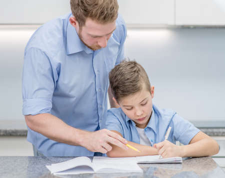 Father helps his son doing homework at home.