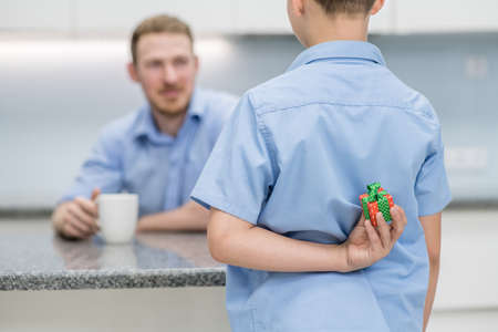 Young boy holds gift box behind his back for dad. Father day concept.