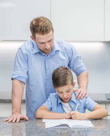 Young boy doing his school homework with his father at home.