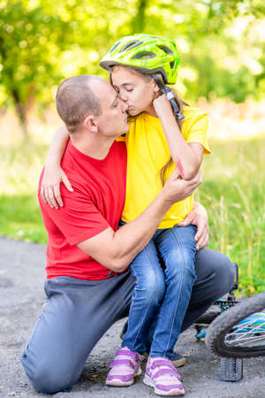 father calms the girl fell from a bicycle. Imagens - 155155244
