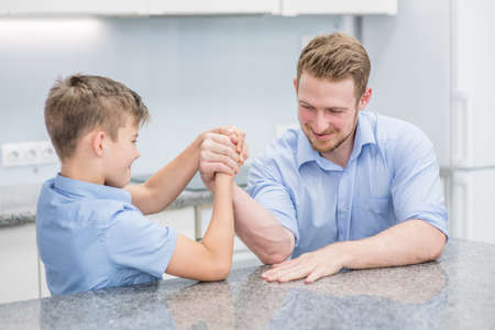 Happy father and son competing in arm wrestling at home. Imagens - 155155086