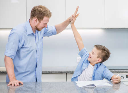 Father and son give high five to each other after doing their homework.