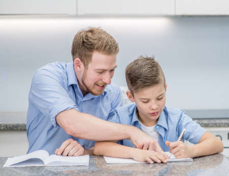 Father and his son doing homework together at home. Imagens - 155155064