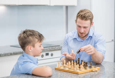 Father teaches son to play chess. Imagens - 155155249