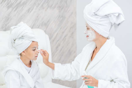 Young woman cleans her daughter's face with a cotton pad and lotion at home. Imagens - 155155093