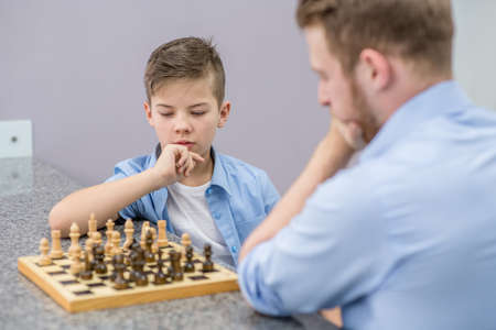 Father and son are playing chess at home.