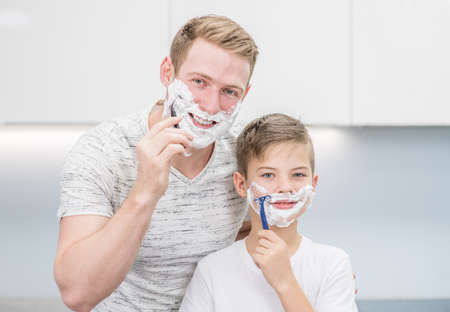Father and young son shave in front of a mirror. Imagens