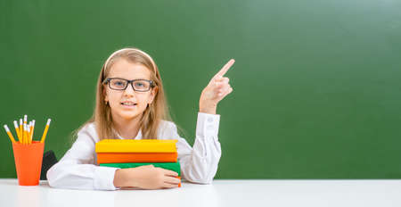 Young girl wearing a eyeglasses sits with books and points away on empty green chalkboard. Empty space for text.