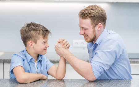 Happy father and son competing in arm wrestling at home.