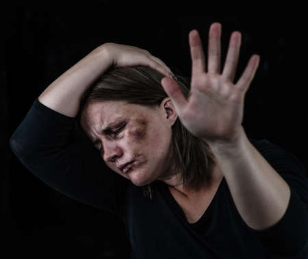 Crying woman victim of domestic violence and abuse showing a stop sign with her hand. Isolated on dark background. Imagens
