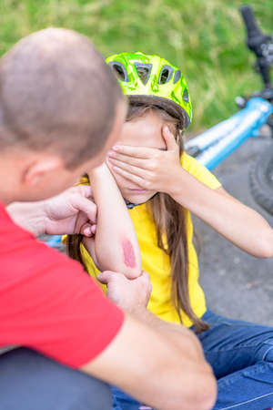 Little girl shows father wound on elbow after falling from bicycle.