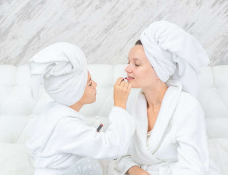 Happy family at home. Mother and daughter are doing make up and having fun sitting on the bed at home. Mom and child girl are in bathrobes and with towels on their heads.