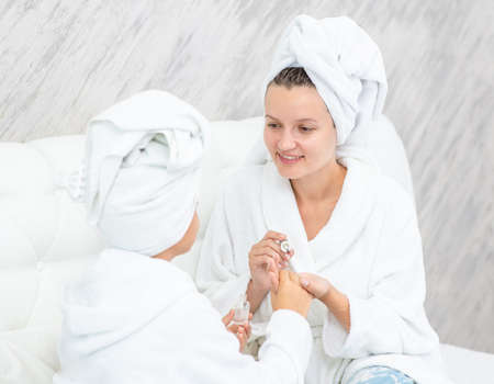 Young woman and her daughter are doing manicures at home. Mom and child girl are in bathrobes and with towels on their heads.