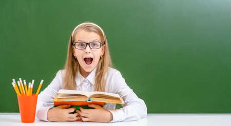 Surprised girl wearing a eyeglasses sits near empty chalk board with books. Empty space for text. Imagens