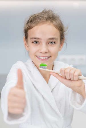 Smiling young girl holds toothbrush and shows thumbs up gesture at home. Imagens