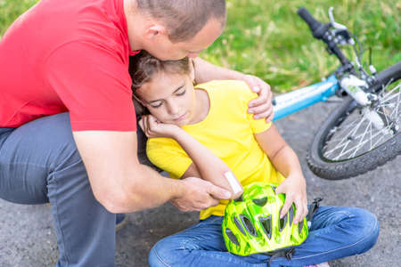 Father comforts a girl who fell off a bicycle.