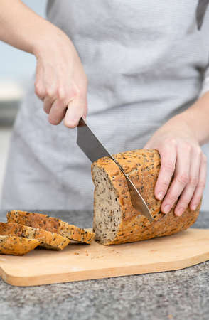 Woman`s hands slicing home-made bread at kitchen.