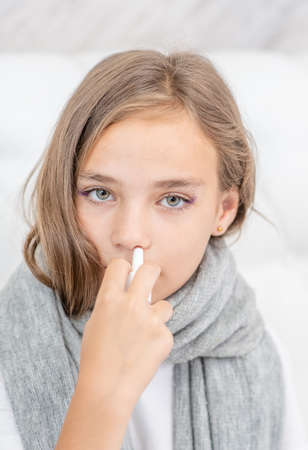 Close up Sick girl with flu using nose spray at home.