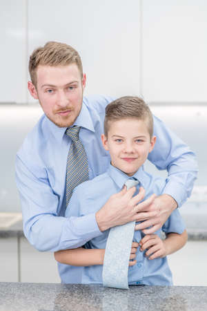 Smiling father helps his son to put his tie at home.