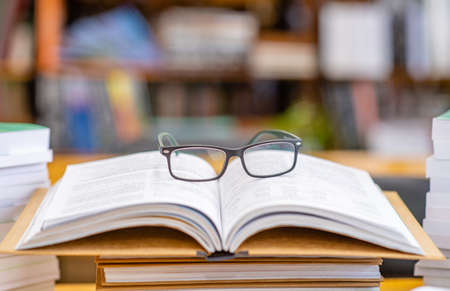 Eyeglasses lies on open book in a library.