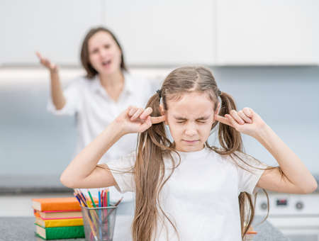 Mother scolds her daughter. Girl covers her ears and closed eyes. Family relationships. Stok Fotoğraf