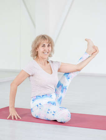 Senior woman stretches legs in a yoga studio. Sport healthy concept.