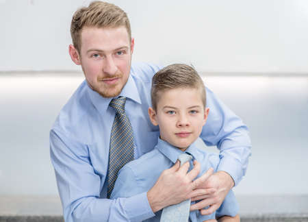 Happy family at home. Father helps his son to tying necktie at home.