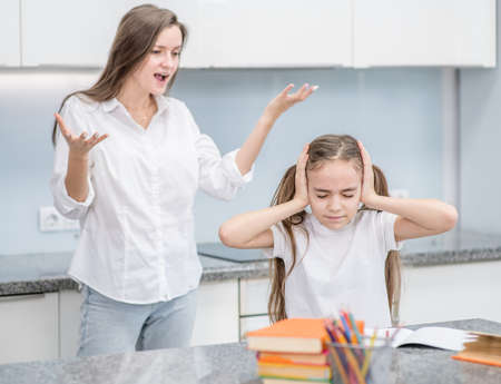 Teen girl covers her ears and stands with closed eyes while her mother scolds her for poor study. Family relationships.