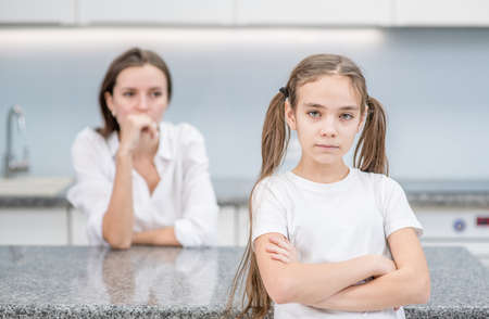 Sad girl and her mother stand at home after they quarreled. Family relationships.