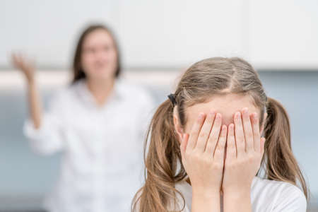 Teen girl covers her face and cies while her mother scolds her. Family relationships. Stok Fotoğraf