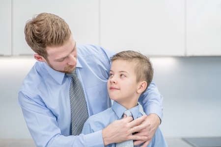 Father helps his son to tying necktie at home. Archivio Fotografico