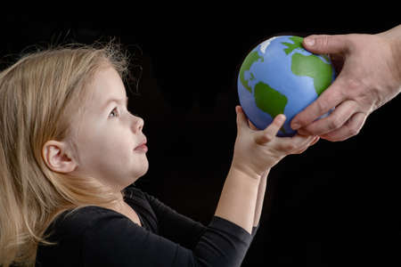 Mother gives the planet into the hands of a child. Isolated on dark background.