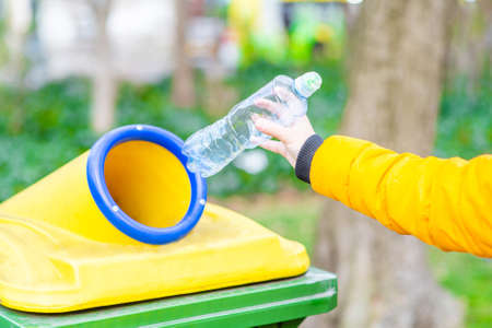 Close up hand throwing empty plastic bottle into the trash. Ecology and recycling concept.