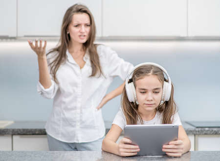 Woman scolds her teenage daughter, girl is listening to music in headphones or play computer game and ignoring her mom. Family relationships.