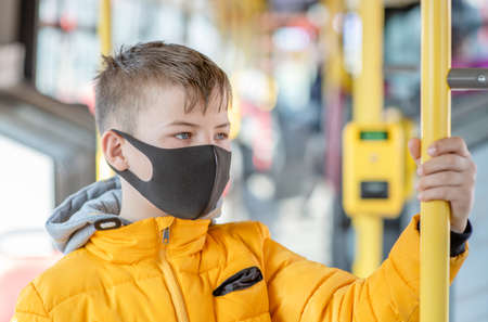 Young boy wearing protective mask holding on to the handrail in the bus.