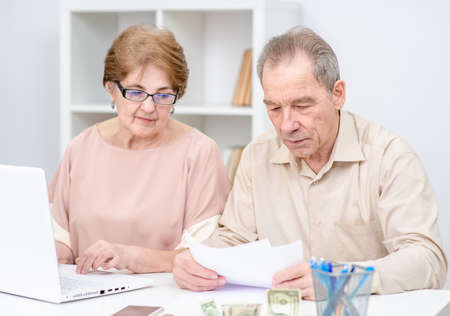 Serious elderly couple calculating bills to pay or doing the income tax declaration online.