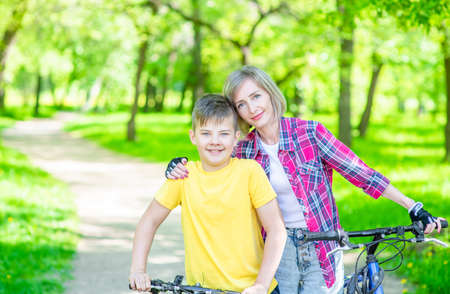 Sporty family leisure. Happy mother embraces her young son, who ride bikes in a summer park. Empty space for text. Archivio Fotografico