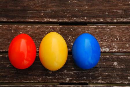 Easter eggs on wooden table Blue, Orange, Yellow Standard-Bild