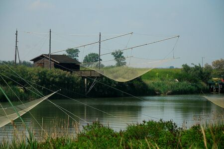 Fishing nets on a river in Italy Standard-Bild