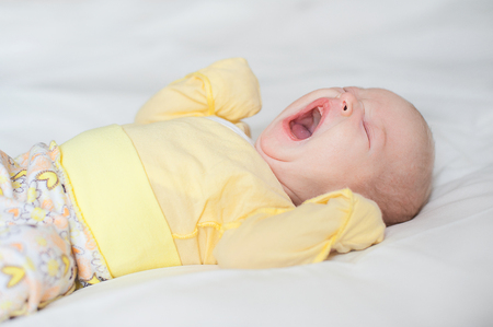 doze: Cute baby girl yawns on a white background Newborn on bed