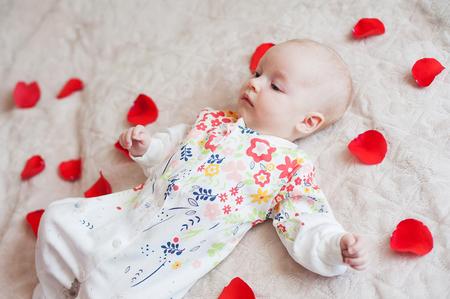 coy: Cute baby girl lies in flower petals bed