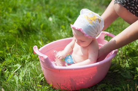 Outdoor baby bathing. Girl in little plastic basin. Baby girl shower in basin with nature green background. Summer cute baby.