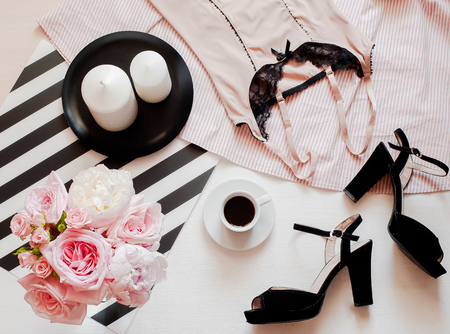 Flat lay, magazines, social media. Top view black lace lingerie. Beauty blog concept. Woman fashion accessories, underwear, bouquet of roses and pions, parfume, jewelry, coffee on white bed background Stockfoto