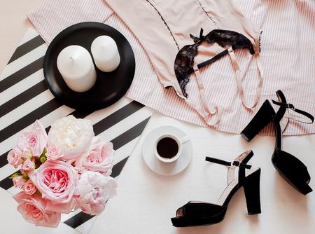 Flat Lay, Zeitschriften, Social Media. Draufsicht schwarze Spitzenwäsche. Beauty-Blog-Konzept. Damenmode-Accessoires, Unterwäsche, Strauß Rosen und Pionen, Parfum, Schmuck, Kaffee auf weißem Betthintergrund Standard-Bild