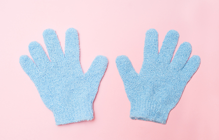 Woman exfoliating hydro glove on pink background. Massage and scrub. Health, spa and beauty concept