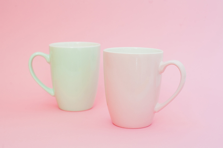 Two cups of coffee stand together to be heart shape on pink background. Mock up, copy space Banco de Imagens