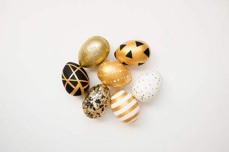 Easter golden decorated eggs isolated on white background. Minimal easter concept. Happy Easter card with copy space for text. Top view, flatlay. Stock Photo